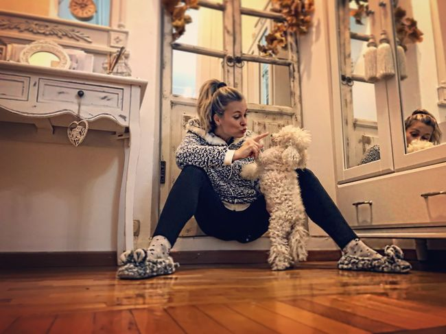 Togetherness Bondo Friendship Confidence  Loyalty Playing Poodletoy Poodle Women Indoors  One Person Hardwood Floor Pets Lifestyles Real People Young Adult Animal Themes Sitting