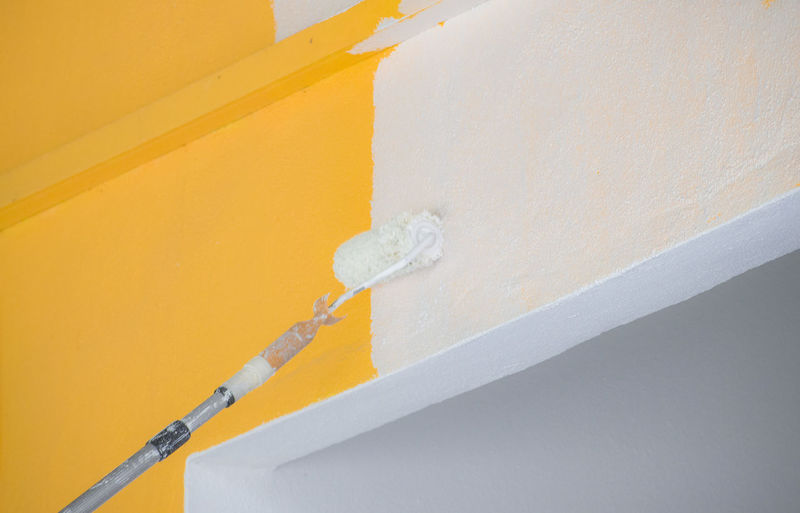 Low angle view of paint roller against wall
