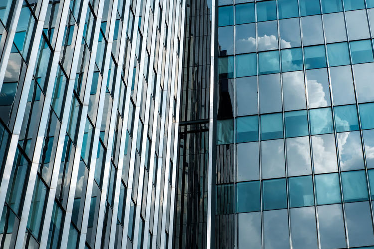 Low angle view of glass building against sky