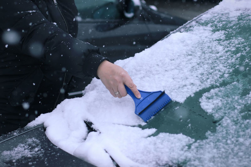 Midsection of woman cleaning snow on car windshield with scraper
