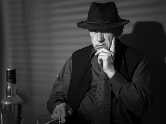 Film Noir reloaded: The dirty old detective in his bureau talking to a new client Acting Adult Hat Alcohol Bottle Day Detective Front View Indoors  Mature Adult Mature Men Men Monochrome Old Person Old Person Sitting One Man Only One Person People Portrait Real People Studio Shot Suit
