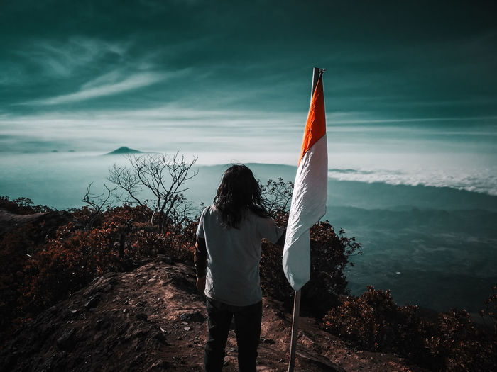 Rear view of man standing by flag on mountain against sky