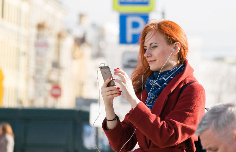 A woman using her phone Listening To Music Mobile Phone Answer The Call Communication Dialing Holding Lifestyles Mobile Phone One Person Real People Redhead Smart Phone Talking On The Phone Technology Telecommunications Equipment Telephone Text Messaging Wireless Technology Women Young Women