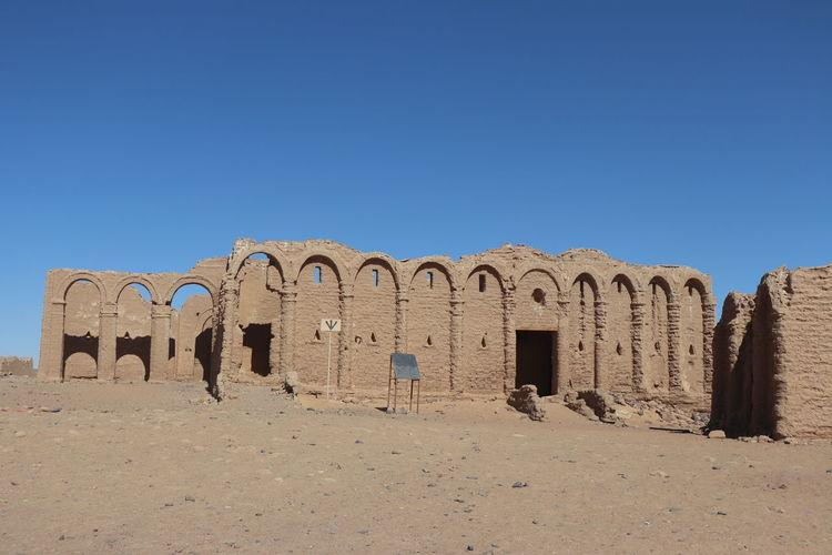 Castle on desert against clear blue sky