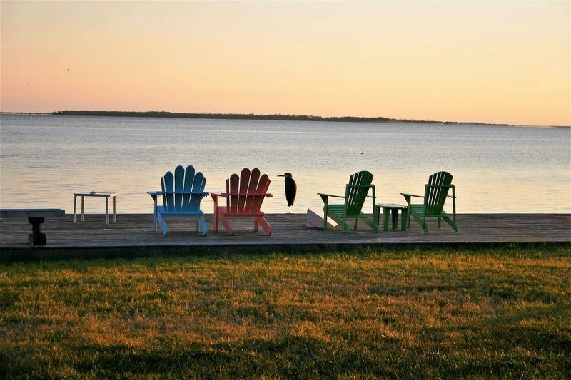 Sky Sunset Water Nature Tranquility Sea Beauty In Nature Land Scenics - Nature Tranquil Scene Beach Grass Horizon Plant No People Seat Orange Color Copy Space Chair Outdoors Adirondack Chairs Egret With Ocean Background Dock Ripples In The Water Relaxing View