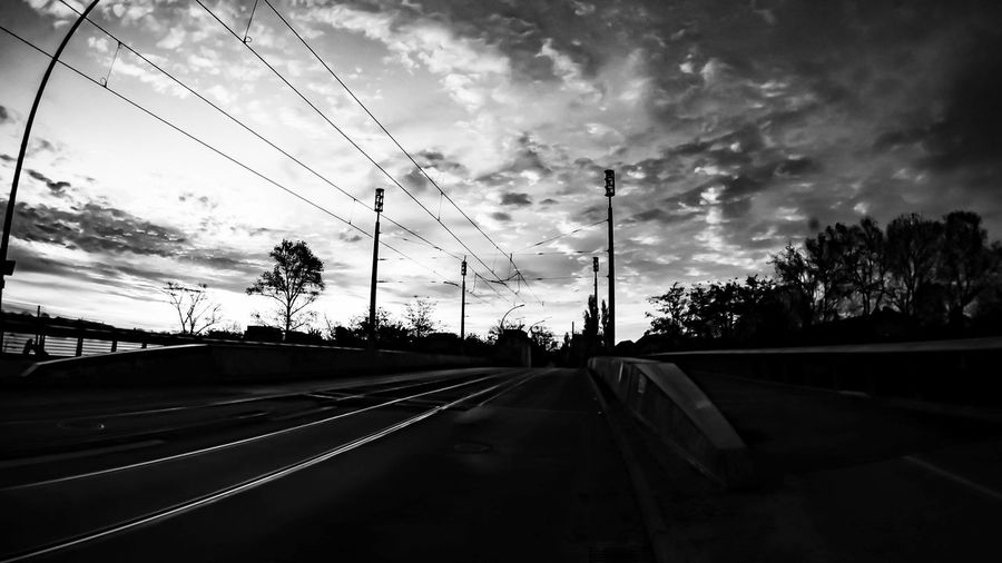 Road by railroad tracks against sky during sunset