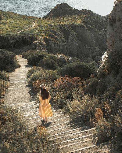 Rear view of woman walking down a hill by long stairway