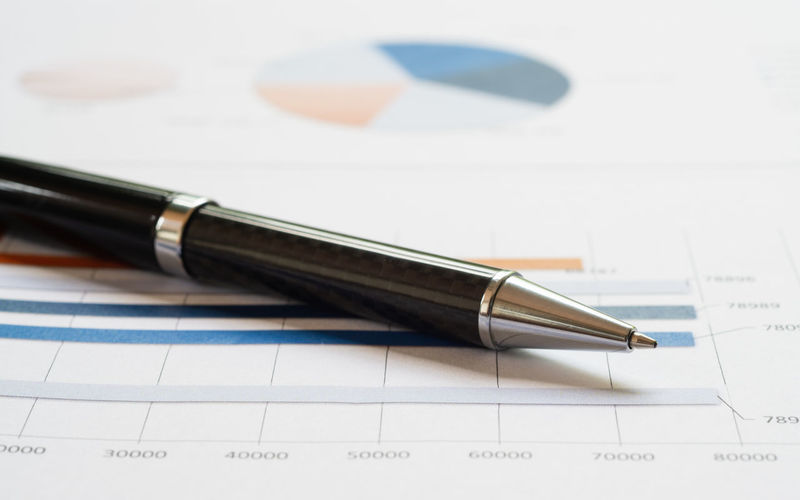 Close-up pen on financial report. Pen Writing Instrument Paper No People Still Life Close-up Business Indoors  Fountain Pen Document Table Ballpoint Pen Focus On Foreground Office Diagram Corporate Business Nib Copy Space Finance Analysis Investment Anaytics Planning Chart Graph