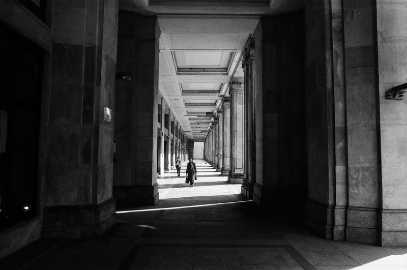 Analog; Nikon FM2 / Ilford PAN 100 The Art Of Street Photography The Week on EyeEm Capture The Moment Everyday Life Nikonphotography Analogue Photography Film Photography Grain Ilford Light And Shadow Warsaw Architecture Direction The Way Forward Built Structure Architectural Column Arcade Indoors  Building Corridor Day History The Past Incidental People Old Real People Diminishing Perspective In A Row Arch Colonnade