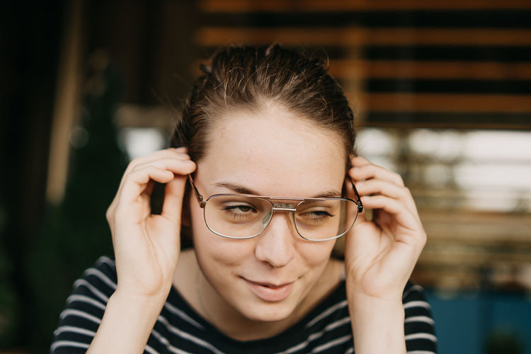Casual Clothing Child Close-up Contemplation Eyeglasses  Focus On Foreground Front View Glasses Hairstyle Headshot Human Body Part Human Face Indoors  Lifestyles Looking At Camera One Person Portrait Real People Smiling Striped Teenager Young Adult