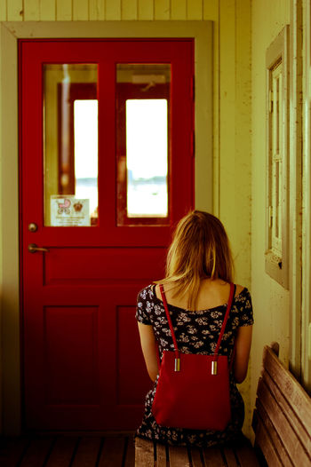 Rear view of young woman standing at home