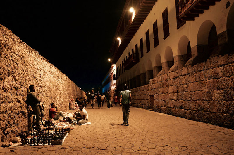 People walking on street amidst buildings at night