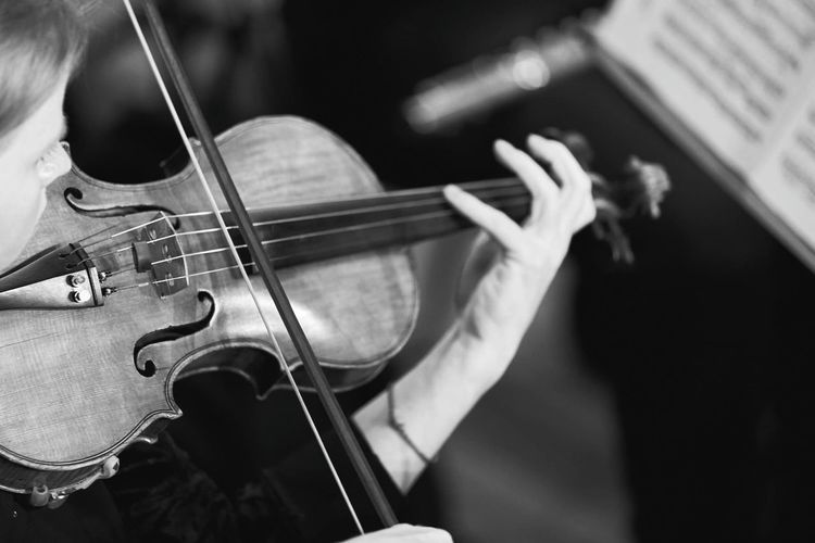 High angle view of mid adult woman playing violin while sitting indoors