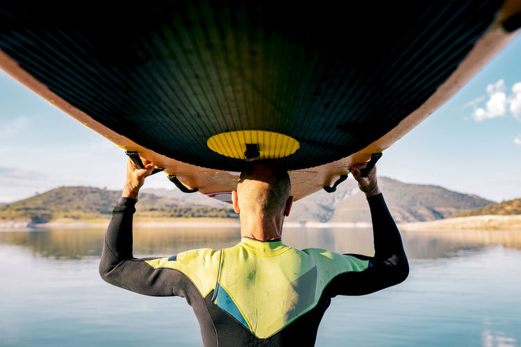 Rear view of man holding boat in lake against sky