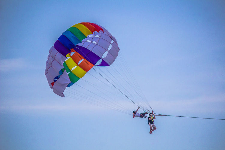 Adventure Leisure Activity Multi Colored Flying Mid-air Lifestyles Low Angle View Extreme Sports Tourist Transportation Parachute Tourism Sky Travel Freedom Enjoyment Paragliding Parasailing Office Art Art For Sale Wallart India Inspired Stills Magazine Water
