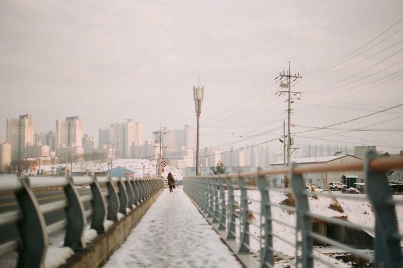 Woman walking on snowy footbridge against sky