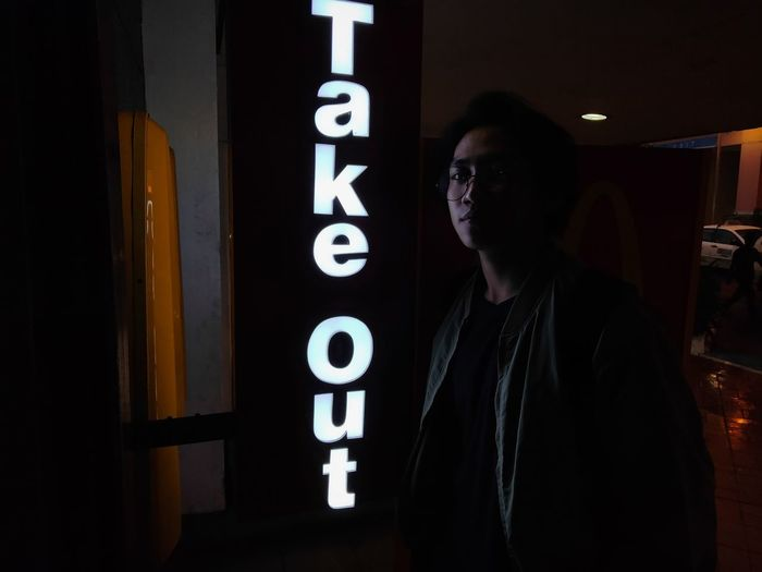 Side view of man standing in illuminated text