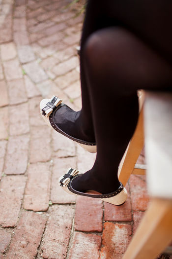 Woman showing slim legs in black stockings High Heels Low Section Human Leg Shoe Human Body Part Body Part One Person Fashion Women Adult Sitting Lifestyles Human Limb Limb Footpath Selective Focus Day Human Foot Outdoors Brick Paving Stone Blackandwhite Stockings Sexygirl Slim
