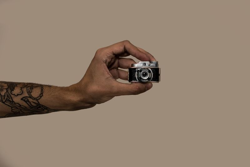 Cropped hand of man holding toy camera against beige background