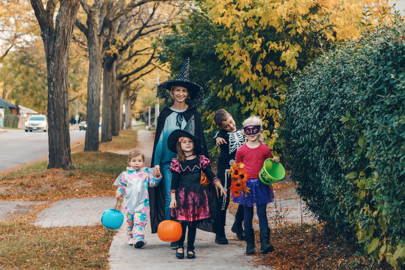 Trick or treat. mother with children going to trick or treat on halloween holiday.