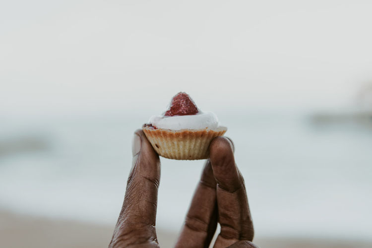 Close-up of hand holding a cup cake against sky