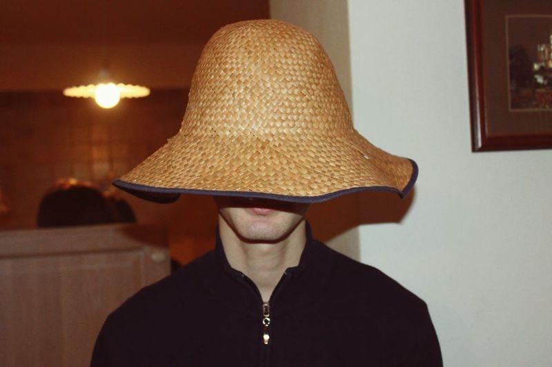Man Wearing Wicker Hat In Illuminated Room