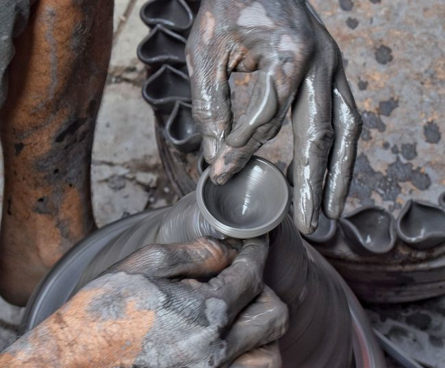 Cropped Messy Hands Of Potter Making Oil Lamps On Pottery Wheel