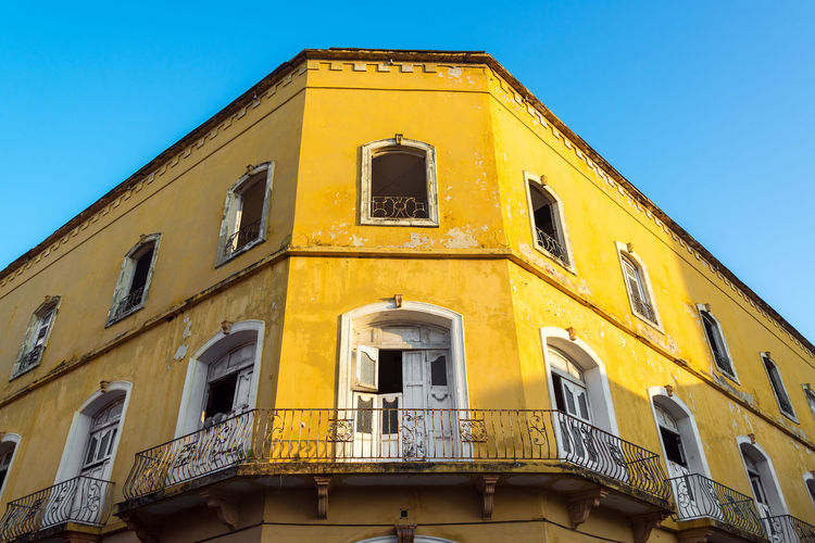 Low angle view of yellow abandoned building against clear sky