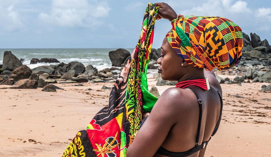 Ghana woman walking around on the beautiful beach of axim, located in ghana west africa