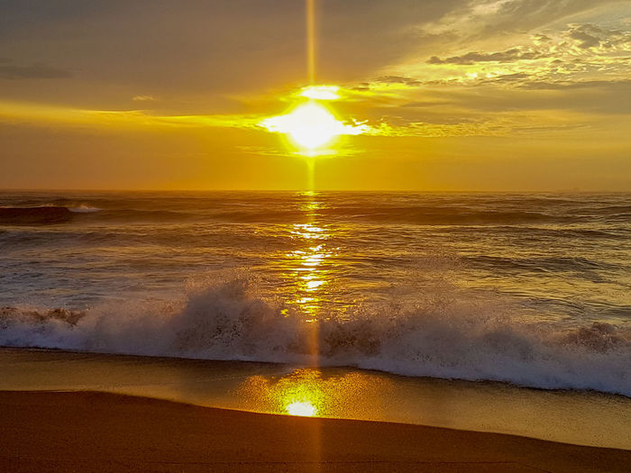 A dramatic sunrise. Colors Evening Sand Day Light Outdoors Backlight Tide Morning Sky Dawn Weather Ocean Sea Sunrise Sun Dramatic Sky Cloud - Sky Reflection Water Wave Sea Multi Colored Beach Horizon Yellow Gold Colored Tide Coast Seascape
