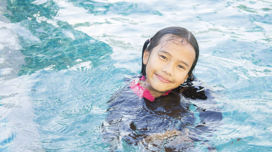 enjoy swimming Cheerful Childhood Day Elementary Age Girls Happiness Headshot High Angle View Leisure Activity Lifestyles Looking At Camera Nature One Person Outdoors People Portrait Real People Smiling Swimming Swimming Pool Vacations Water Waterfront Young Adult