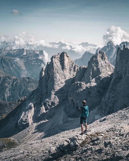 Backpacker standing on mountain against sky