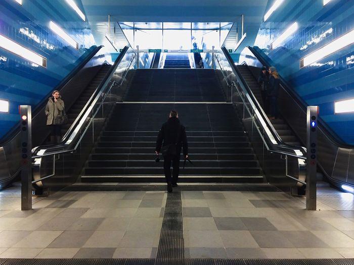 Full length of woman walking on escalator