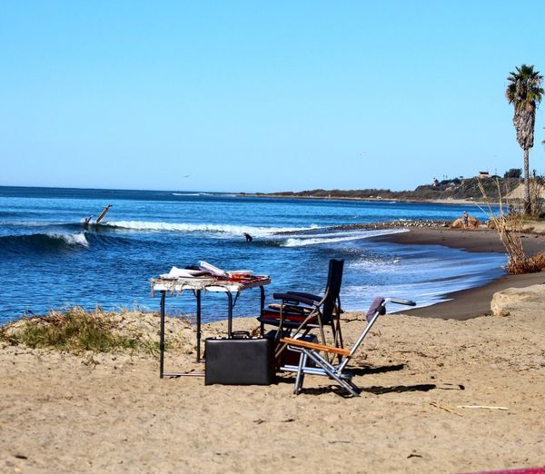 Empty chairs and table on calm beach