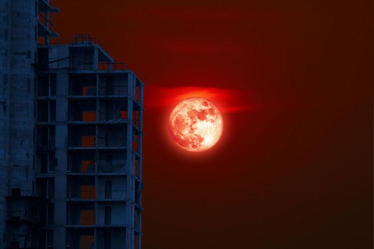 Illuminated building against sky during sunset