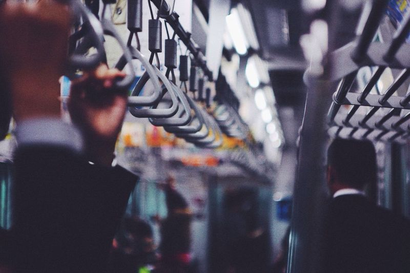 Cropped image of people holding handles in subway train