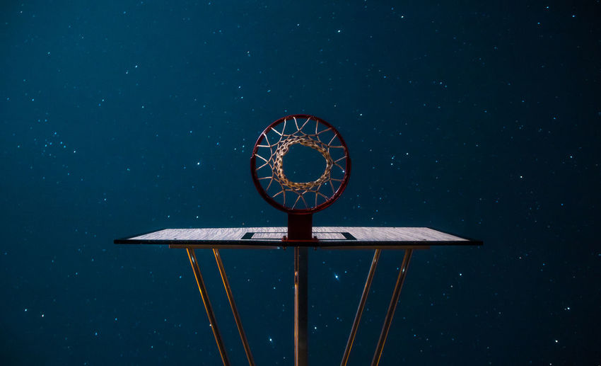 Directly below view of basketball hoop against constellation in sky
