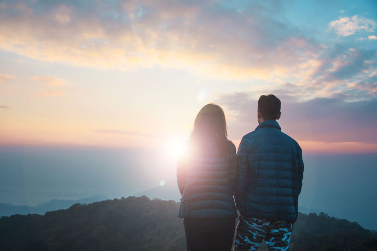 Rear view of couple standing on mountain against cloudy sky during sunset