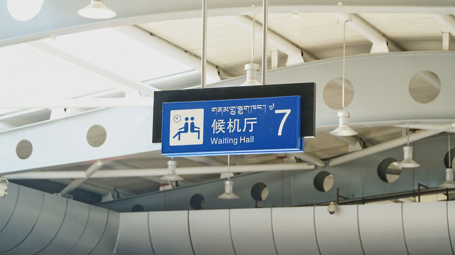 Waiting Hall Sign with Chinese and Tibet language Air Vehicle Airplane Airport Airport Terminal Arrival Arrival Departure Board Arrow Symbol Ceiling Communication Guidance Indoors  Information Information Sign Low Angle View Mode Of Transportation No People Script Sign Text Transportation Travel Western Script