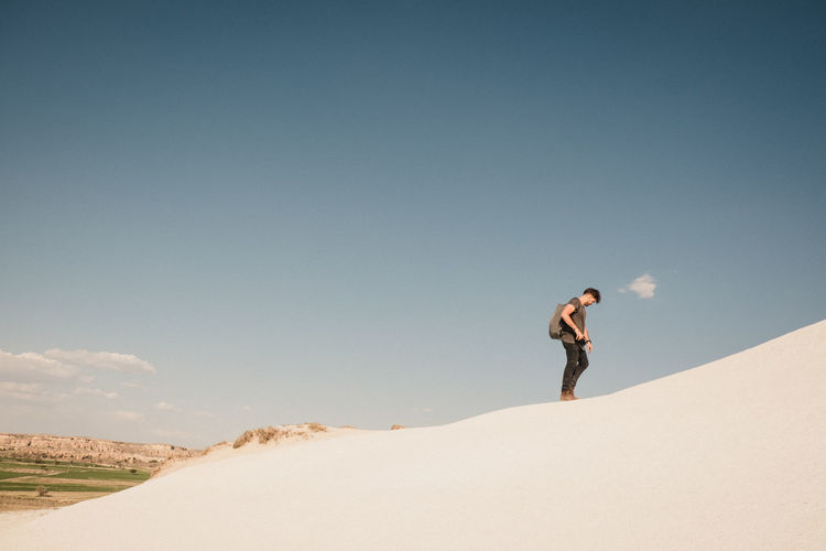 Young man walking in desert against sky