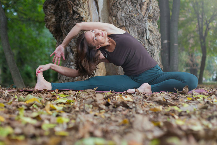 Full length of woman lying on tree trunk during autumn
