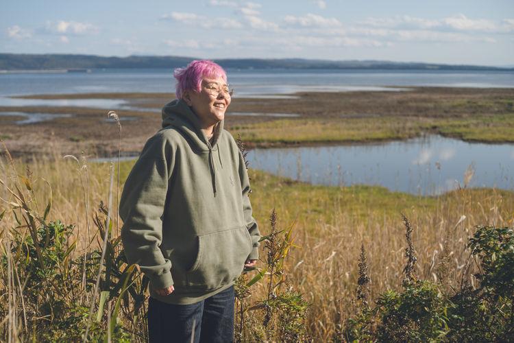 Woman standing on field by marshy area at hokkaido, japan