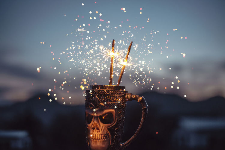 Close-up of sparklers in mug against sky
