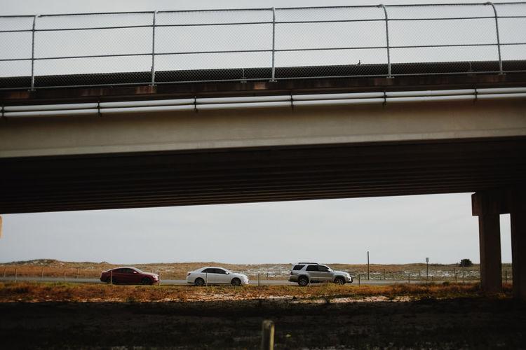 Cars on bridge against sky