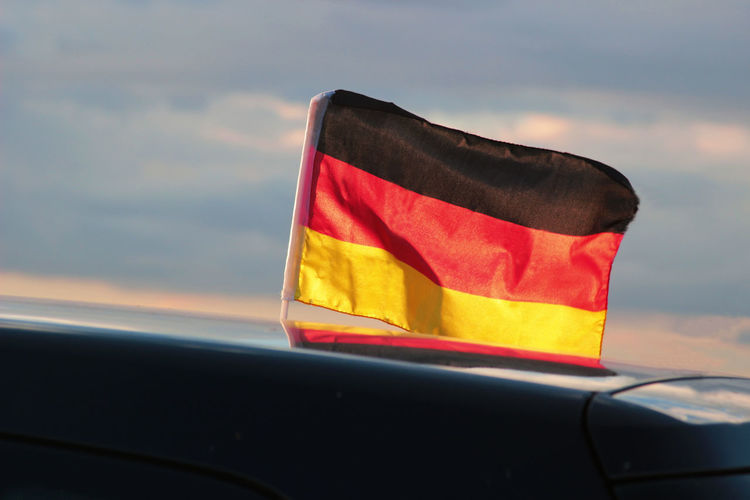 German flag flattering from a car roof Black, Red & Gold German Nationalism Roof Soccer World Cup Supporters Of Sweden Car Car Roof Cloud - Sky Colorful Fan Flag Flattering Flying Germany No People Outdoors Patriotism Pride Prideparade Sky Soccer Sunset Waving Wind