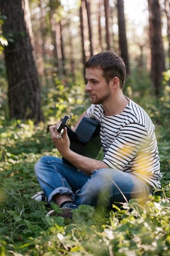 Portrait of young man using mobile phone in forest