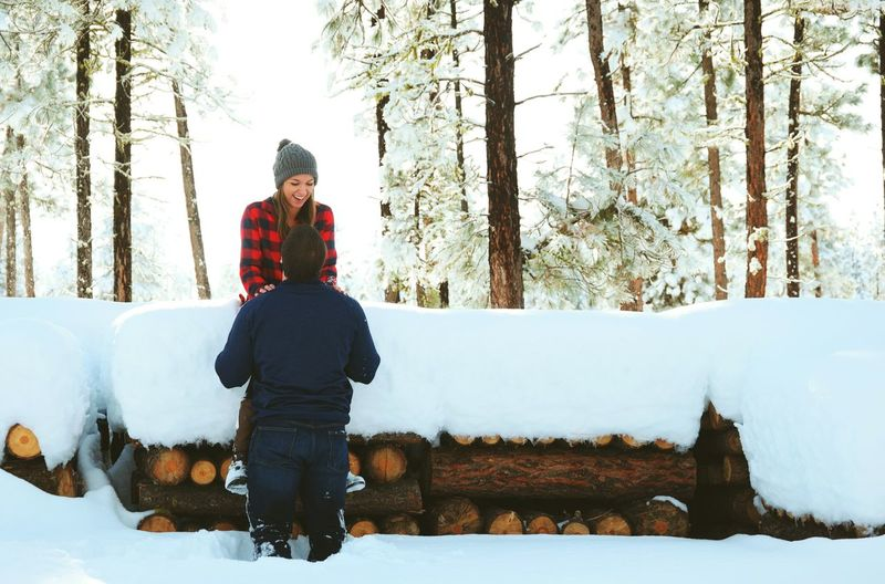 Happy couple with child standing by snow covered stacked logs in forest