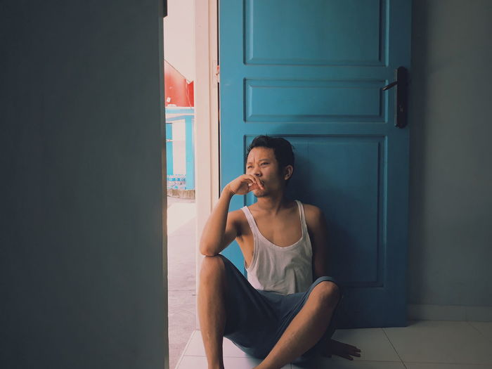 Young woman looking away while sitting on door of home