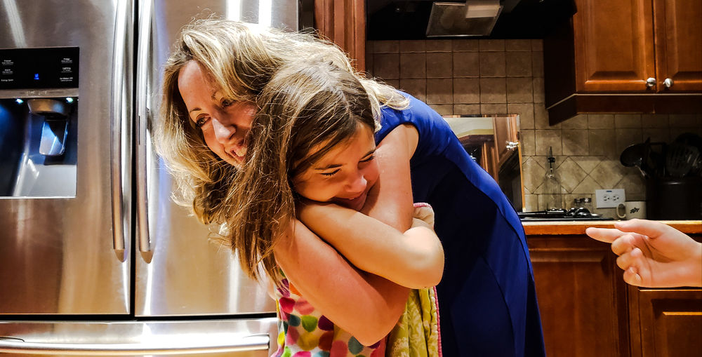 Mother and daughter embracing in kitchen at home