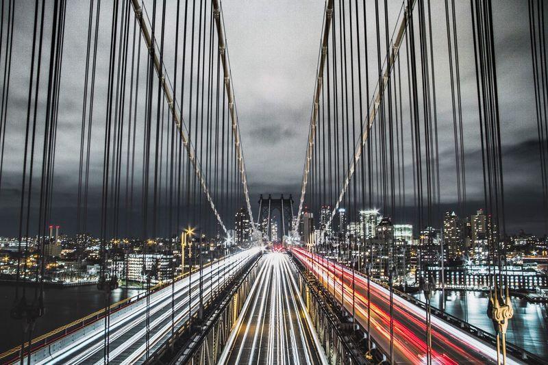 Panoramic view of suspension bridge over city at night